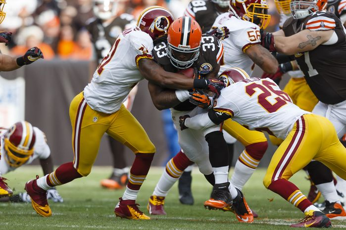 Cleveland Browns running back Trent Richardson (33) runs the ball as Washington Redskins cornerback Josh Wilson (26) and free safety Madieu Williams (41) tackle him during an NFL football game in Cleveland, Sunday, Dec. 16, 2012. (AP Photo/Rick Osentosk