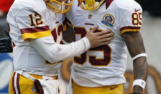 Washington Redskins quarterback Kirk Cousins (12) congratulates wide receiver Leonard Hankerson after a 54-yard touchdown pass in the first quarter of an NFL football game against the Cleveland Browns in Cleveland, Sunday, Dec. 16, 2012. (AP Photo/Rick Osentoski)
