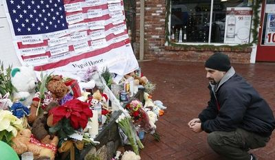 Mark Sorrentino of Naugatuck, Conn., pays his respects near a U.S. flag with the names of the school-shooting victims on a makeshift memorial in the Sandy Hook village of Newtown, Conn., on Monday, Dec. 17, 2012. (AP Photo/Julio Cortez)