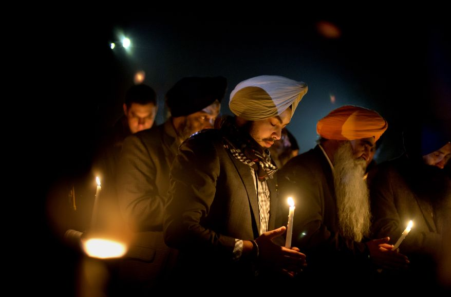 Varinder Singh of the Queens borough of New York joins a group of Sikhs from around the Northeast in a moment of prayer on Sunday, Dec. 16, 2012, in Newtown, Conn., as a memorial service is broadcast over a loudspeaker outside Newtown High School for the victims of the Sandy Hook Elementary School shootings. (AP Photo/David Goldman)
