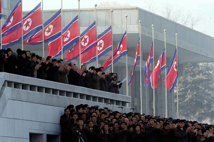 North Koreans clap near their country's flags flown at half-staff during a reopening ceremony at the Kumsusan Palace of the Sun in Pyongyang, North Korea, on Monday, Dec. 17, 2012. North Korean officials reopened the mausoleum on the first anniversary of the death of former leader Kim Jong-il. (AP Photo/Ng Han Guan)