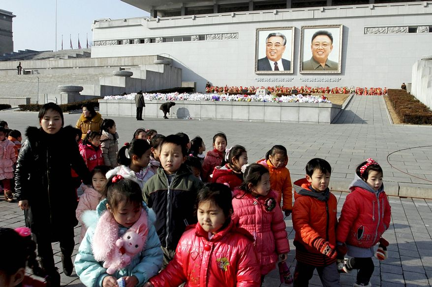 North Korean children leave after laying flowers before portraits of the late leaders Kim Il-sung (left) and Kim Jong-il on Kim Il-sung Square in Pyongyang, North Korea, on Monday, Dec. 17, 2012. (AP Photo/Jon Chol Jin)
