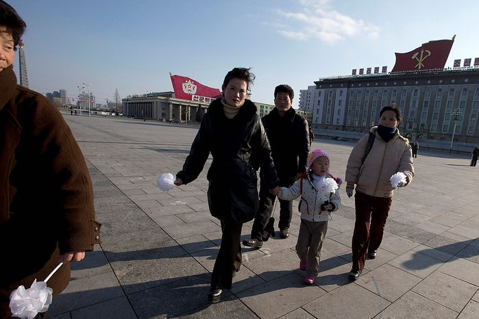 North Koreans arrive to pay their respects to the late leader Kim Jong-il on Kim Il-sung Square in Pyongyang, North Korea, on Monday, Dec. 17, 2012. North Korea marked the first annive