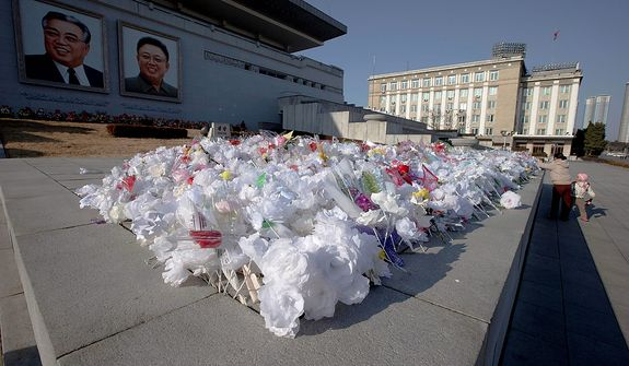 A North Korean woman and a child pay their respects to portraits of the late leaders Kim Il-sung (left) and Kim Jong-il on Kim Il-sung Square in Pyongyang, North Korea, on Monday, Dec. 17, 2012. North Korea marked the first anniversary of the death of Kim Jong-il on Monday. (AP Photo/Ng Han Guan)