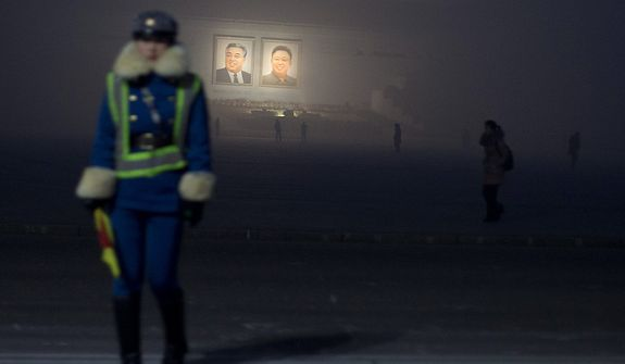 A North Korean traffic coordinator stands on a roadside near portraits of the late leaders Kim Il Sung, left, and Kim Jong Il during a foggy morning on Kim Il Sung Square in Pyongyang, North Korea, Monday, Dec. 17, 2012. North Korea marked the first death anniversary of the former leader Kim Jong Il on Monday. (AP Photo/Ng Han Guan)