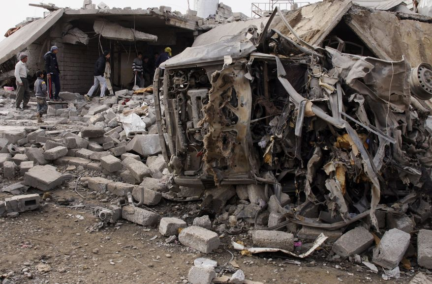 People inspect the scene of a car bomb attack in al-Mouafaqiyah, Iraq, a village inhabited by families from the Shabak ethnic group, near the city of Mosul, 225 miles northwest of Baghdad, on Monday, Dec. 17, 2012. (AP Photo)