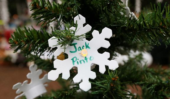 A snowflake ornament with the name of 6-year-old Jack Pinto hangs on a Christmas tree at a makeshift memorial in the Sandy Hook village of Newtown, Conn., on Monday, Dec. 17, 2012, as the town mourns victims killed in Friday's school shooting. Jack, who was killed when gunman Adam Lanza opened fire inside the Sandy Hook Elementary School, will be buried Monday. (AP Photo/Julio Cortez)