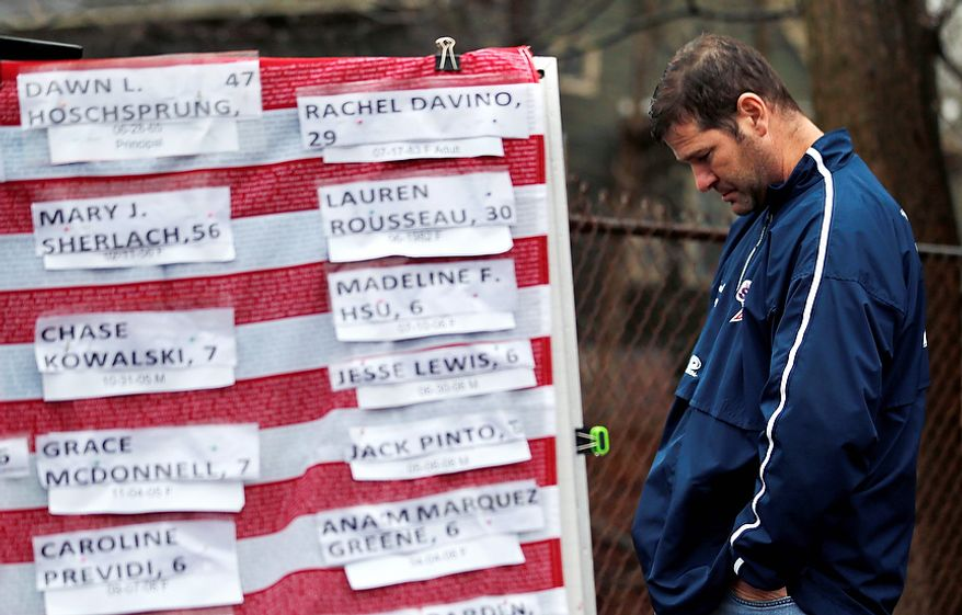 A man pays his respects near a U.S. flag with the names of victims on a makeshift memorial in the Sandy Hook village of Newtown, Conn., on Monday, Dec. 17, 2012, as the town mourns victims of Friday's school shooting. (AP Photo/Julio Cortez)