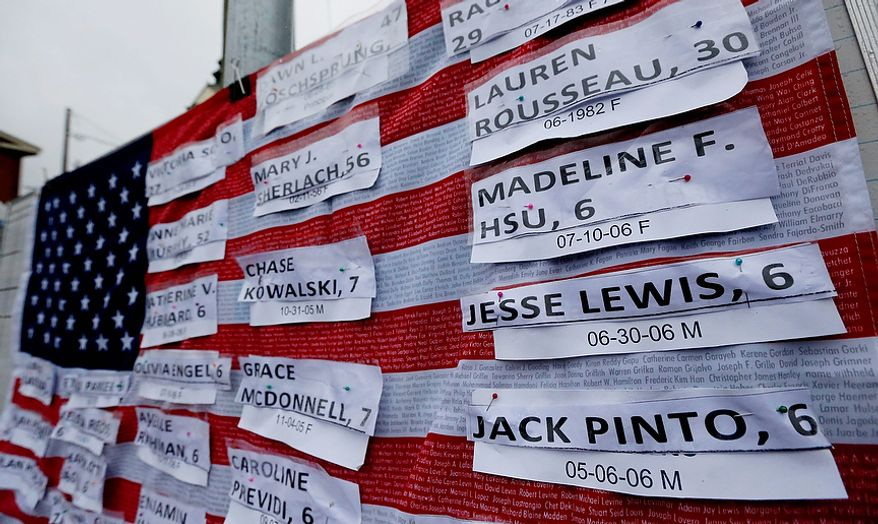 Names of victims hang on a U.S. flag on a makeshift memorial in the Sandy Hook village of Newtown, Conn., on Monday, Dec. 17, 2012, as the town mourns those killed in Friday's school shooting. (AP Photo/Julio Cortez)