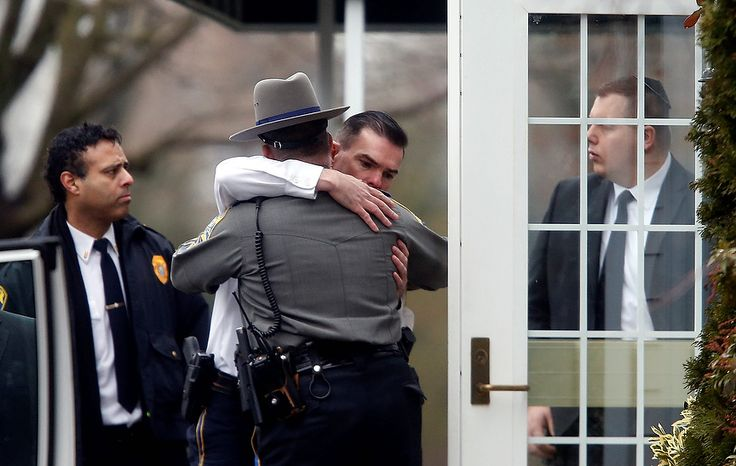 Police officers comfort one another outside a funeral service for 6-year-old Noah Pozner, Monday, Dec. 17, 2012, in Fairfield, Conn. Pozner was killed when a gunman walked into Sandy Hook Elementary School in Newtown Friday and opene