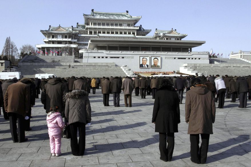 North Koreans observe a moment of silence as they bow before portraits of the late leaders Kim Il-sung (left) and Kim Jong-il on Kim Il-sung Square in Pyongyang, North Korea, on Monday, Dec. 17, 2012. Sirens wailed for three minutes at noon Monday in honor of the first anniversary of the death of Kim Jong-il. (AP Photo/Jon Chol Jin)