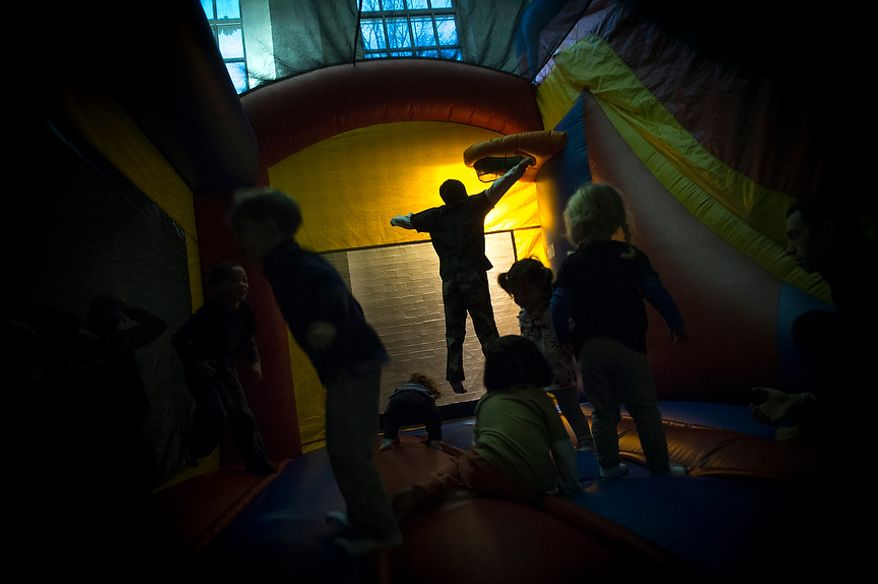 "Kids play in the ""moon bounce"" during the Chanukah Carnival at the Washington, D.C., Jewish Community Center on Sunday, Dec. 9, 2012. Approximately 100 people came to enjoy arts and crafts, dreidel games, food and even a doughnut-walk contest. (Rod Lamkey Jr./The Washington Times)"
