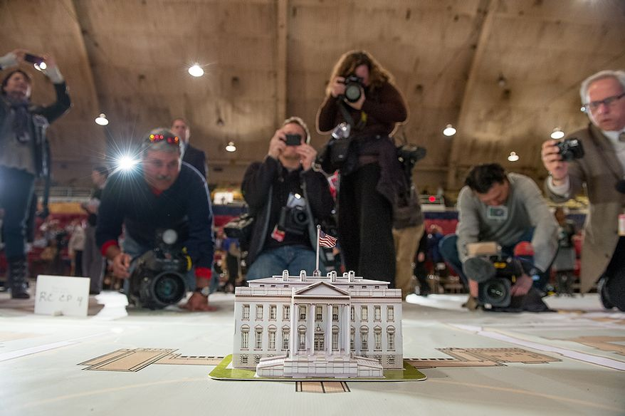 Members of the media crowd around a model of the White House as the Joint Task Force-National Capital Region and the D.C. National Guard hold a final Inauguration Day planning symposium using a 40-by 60-foot map of downtown Washington and the National Mall on Wednesday, Dec. 12, 2012, in Washington. The inaugural events are planned out for months with a number of different military and civilian organizations.  (Andrew Harnik/The Washington Times)