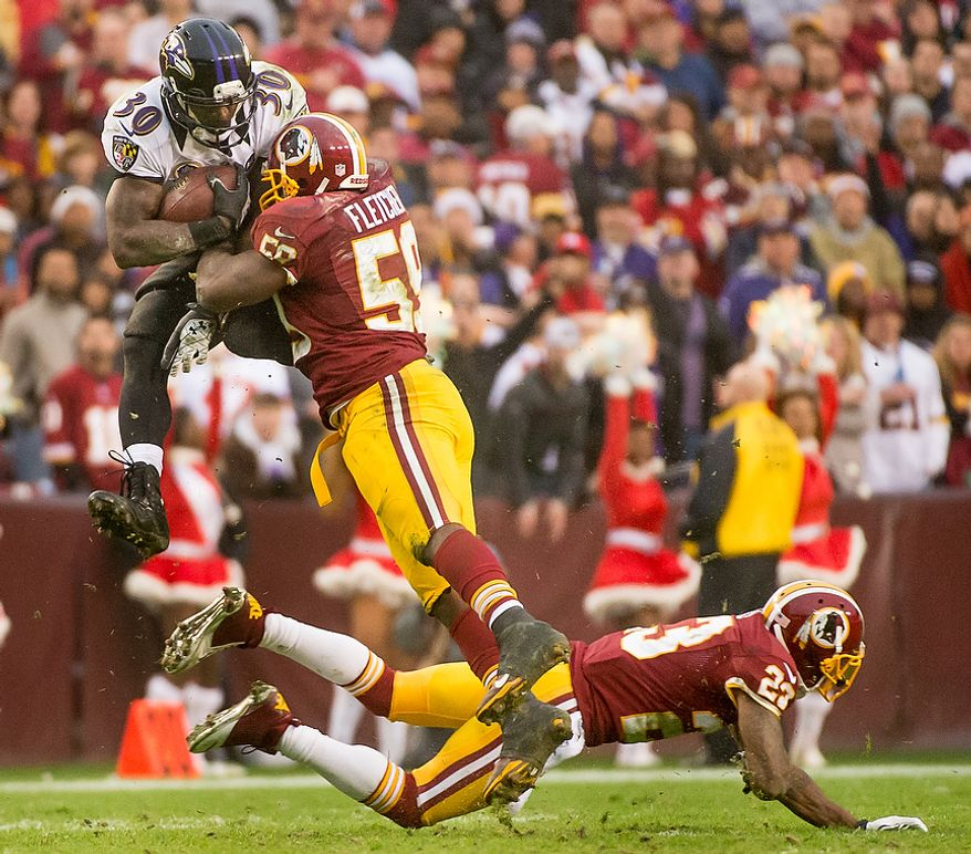 Baltimore Ravens running back Bernard Pierce (30) is tackled by Washington Redskins inside linebacker London Fletcher (59) as he jumps over Redskins cornerback DeAngelo Hall (23) on an 11-yard pass play in the fourth quarter of a game at Fedex Field in Landover, Md., on Sunday, Dec. 9, 2012. (Andrew Harnik/The Washington Times)