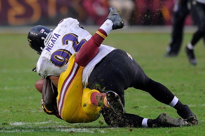 Washington Redskins quarterback Robert Griffin III (10) injures his right leg as he is tackled by Baltimore Ravens defensive end Haloti Ngata (92) in the fourth quarter at FedEx Field in Landover, Md., on Sunday, Dec. 9, 2012. (Preston Keres/Special to The Washington Times)