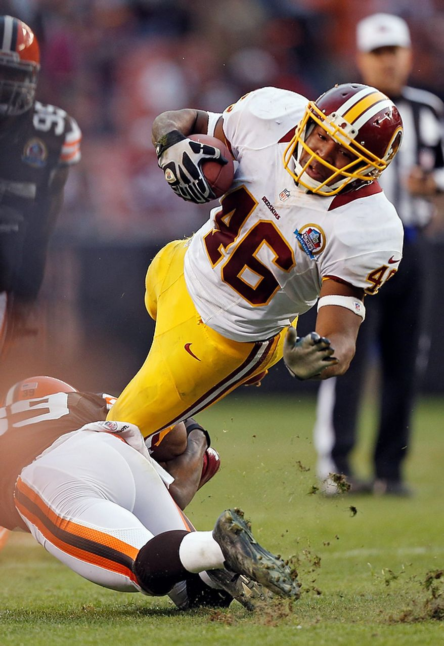 Washington Redskins running back Alfred Morris (46) is tripped by Cleveland Browns cornerback Tashaun Gipson in the fourth quarter of an NFL football game in Cleveland, Sunday, Dec. 16, 2012. Morris rushed for 87 yards and two touchdowns in the Redskins' 38-21 win.(AP Photo/Rick Osentoski)