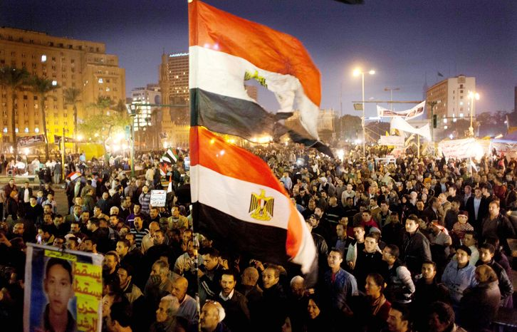 Egyptians opposing President Mohammed Morsi carry flags in Tahrir Square, Cairo, on Tuesday. (Associated
