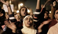 Egyptians opposing President Mohammed Morsi chant in Tahrir Square, Cairo, on Tuesday. Early results from the first round of voting on a draft constitution showed 56 percent in favor. The opposition fears that a large Islamist constituency in rural and upper Egypt will back it in the second round. (Associated Press)