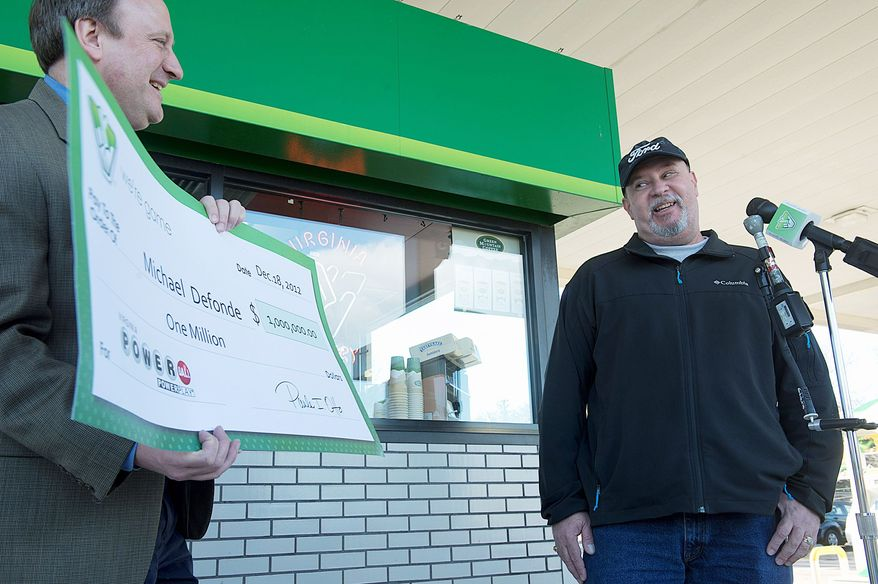 Michael DeFonde is amused Tuesday at a BP gas station in Woodbridge by the size of his Powerball winnings as he looks at a check held by Virginia Lottery spokesman John Hagerty. Mr. DeFonde says he always buys his tickets and gas at the BP, located on Maple Dale Avenue. (Barbara L. Salisbury/The Washington Times)