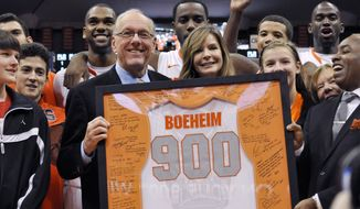 Syracuse coach Jim Boeheim, joined by his wife, Julie, is presented with a jersey for his 900th career win, after Syracuse defeated Detroit 72-68 in an NCAA college basketball game in Syracuse, N.Y., Monday, Dec. 17, 2012. (AP Photo/Kevin Rivoli)