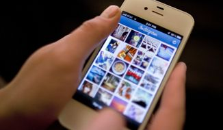 ** FILE ** Instagram is demonstrated on an iPhone on Monday, April 9, 2012, in New York. (AP Photo/Karly Domb Sadof)
