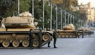 Egyptian army tanks deploy outside the presidential palace during a protest against President Mohammed Morsi in Cairo on Tuesday, Dec. 18, 2012. (AP Photo/Hassan Ammar)