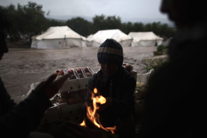 Syrians who fled their homes with their families gather around a fire to warm themselves at a makeshift vegetables store in a camp for the displaced in the village of Atmeh, Syria, on Tuesday, Dec. 18, 2012. (AP Photo/Muhammed Muheisen)