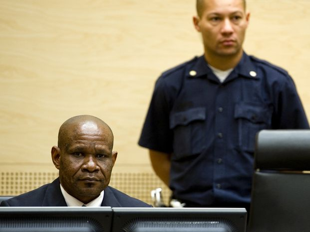 Mathieu Ngudjolo (left), former leader of the National Integrationist Front, awaits the verdict in his war crimes trial at the International Criminal Court in The Hague on Tuesday, Dec. 18, 2012. (AP Photo/Robin van Lonkhuijsen, Pool)