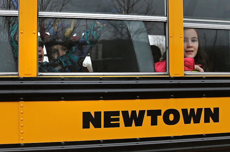 **FILE** Schoolchildren look out the window of their bus as they head back to school in Newtown, Conn., on Dec. 18, 2012. Classes resume Tuesday for Newtown schools except those at Sandy Hook. Buses ferrying students to schools were festooned with large green and white ribbons on the front grills, the colors of Sandy Hook. At Newtown High School, students in sweatshirts and jackets, many wearing headphones, betrayed mixed emotions.  Adam Lanza walked into Sandy Hook Elementary School in Newtown,  Friday and opened fire, killing 26 people, including 20 children, before killing himself. (AP Photo/Charles Krupa)