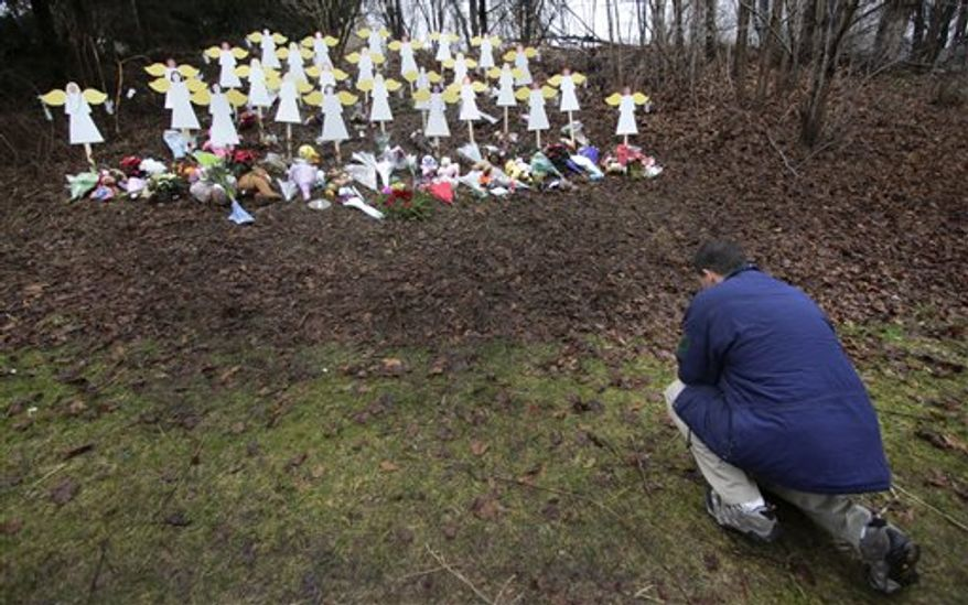 Robert Soltis, of Newtown, Conn., pauses after making the sign of the cross at a memorial to school shooting victims in Newtown, Tuesday, Dec. 18, 2012. Adam Lanza walked into Sandy Hook Elementary School in Newtown, Dec. 14,  and opened fire, killing 26 people, including 20 children, before killing himself. (AP Photo/Charles Krupa)