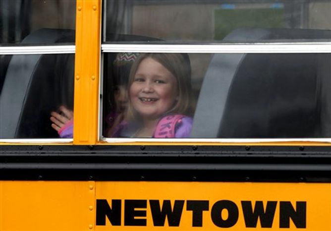A young girl waves as her school bus pulls into Hawley School, Tuesday, Dec. 18, 2012, in Newtown, Conn.  Classes resume Tuesday for Newtown schools except those at Sandy Hook. Buses ferrying students to schools were festooned with large green and white ribbons on the front grills, the colors of Sandy Hook. At Newtown High School, students in sweatshirts and jackets, many wearing headphones, betrayed mixed emotions.  Adam Lanza walked into Sandy Hook Elementary School in Newtown,  Friday and opened fire, killing 26 people, including 20 children, before killing himself.(AP Photo/Jason DeCrow)