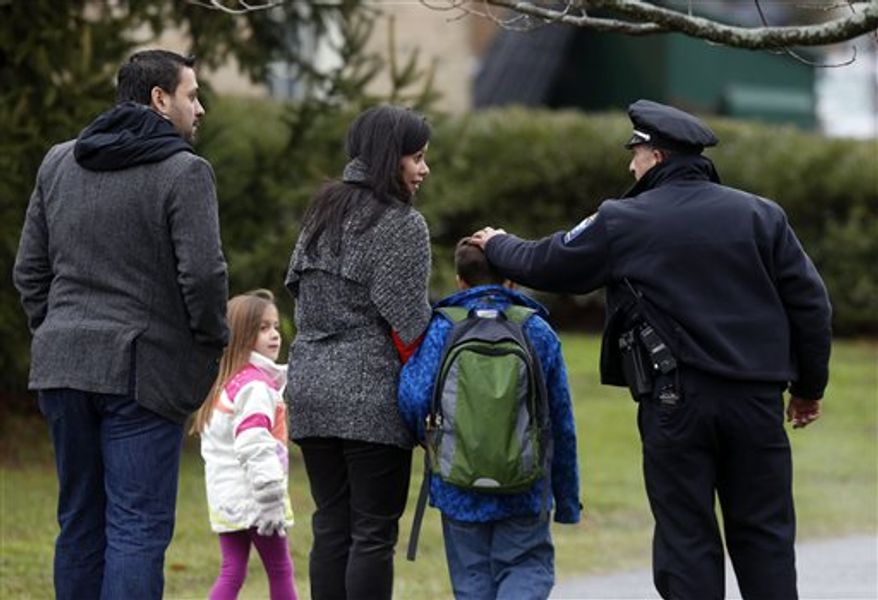 Easton police officer J. Sollazzo greets a returning student as he is walked into Hawley School, Tuesday, Dec. 18, 2012, in Newtown, Conn. Classes resume Tuesday for Newtown schools except those at Sandy Hook. Buses ferrying students to schools were festooned with large green and white ribbons on the front grills, the colors of Sandy Hook. At Newtown High School, students in sweatshirts and jackets, many wearing headphones, betrayed mixed emotions.  Adam Lanza walked into Sandy Hook Elementary School in Newtown,  Friday and opened fire, killing 26 people, including 20 children, before killing himself.(AP Photo/Jason DeCrow)