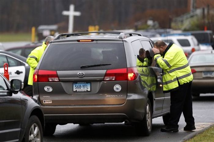 A police officer inspects a vehicle arriving at St. Rose of Lima Roman Catholic Church before funeral services for James Mattioli, a boy killed in an elementary school shooting, Tuesday, Dec. 18, 2012, in Newtown, Conn. Mattioli, 6, was killed when Adam Lanza walked into Sandy Hook Elementary School in Newtown, Conn., Dec. 14, and opened fire, killing 26 people, including 20 children, before killing himself. (AP Photo/Julio Cortez)