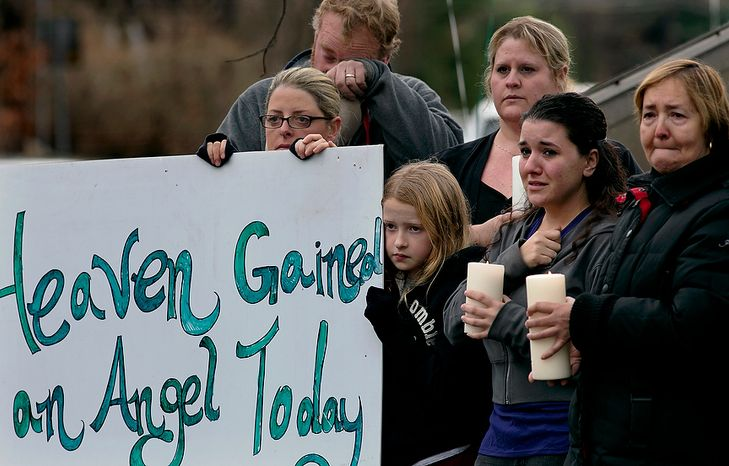 Tom Doyle, back left, standing with family and co-workers, wipes his face as the funeral procession for James Mattioli, 6, who died in the Sandy Hook Elementary School shootings, approaches the St. John's Cemetery Tuesday, Dec. 18, 2012, in Darien, Conn. Center are his wife Debbie and daughter Emily, 10. Adam Lanza opened fire Sandy Hook Elementary School in Newtown on Friday, killing 26 people, including 20 children.  (AP Photo/Craig Ruttle)
