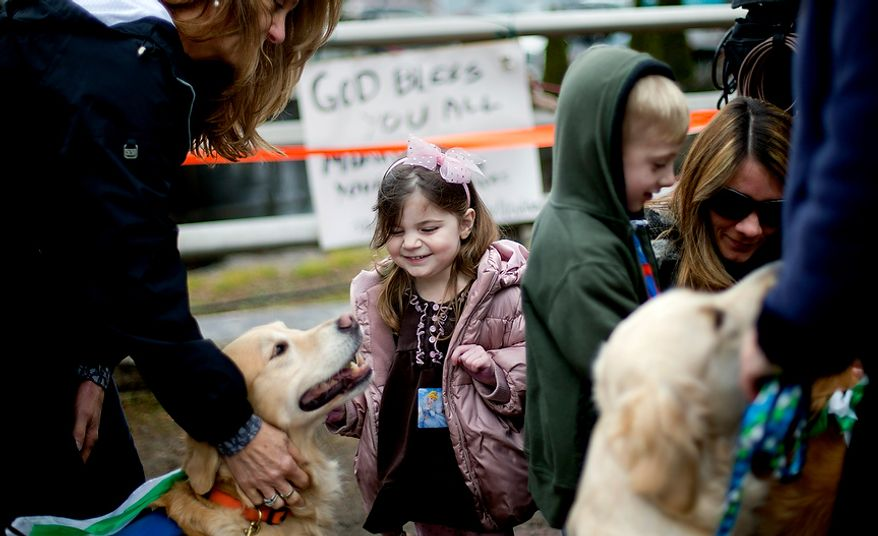 Lily Willinger, 2, of Newtown Conn., pets Libby, a golden retriever therapy dog, during a visit from the dogs and their handlers to a memorial for the Sandy Hook Elementary School shooting victims, Tuesday, Dec. 18, 2012, in Newtown, Conn. (AP Photo/David Goldman)