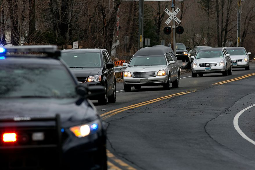 The funeral procession for James Mattioli, 6, who died in the Sandy Hook Elementary School shootings, approaches the St. John's Cemetery Tuesday, Dec. 18, 2012, in Darien, Conn. A gunman walked into Sandy Hook Elementary School in Newtown, Dec. 14,  and opened fire, killing 26 people, including 20 children. Tuesday, Dec. 18, 2012. (AP Photo/Craig Ruttle)