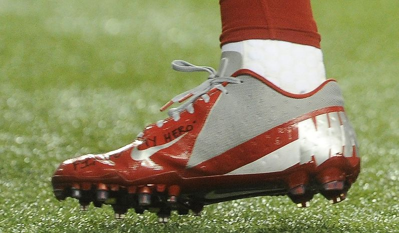 in this Sunday, Dec. 16, 2012, photo, a shoe worn by New York Giants wide receiver Victor Cruz bears a message dedicated to 6-year-old Jack Pinto, one of the victims in last week's school shootings at Sandy Hook Elementary School in Newtown, Conn., as Cruz warms up for the Giants' NFL football game against the Atlanta Falcons in Atlanta. (AP Photo