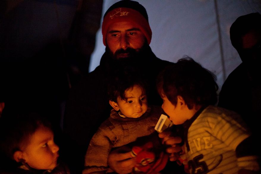 A Syrian man holds his children as they warm themselves at a refugee camp in Azaz, Syria, Monday, Dec. 17, 2012. Thousands of Syrian refugees who fled their homes due to fighting between Free Syrian Army fighters and government forces, face cold weather as temperatures dropped to 2 degrees Celsius (36 degrees Fahrenheit) in Azaz. (AP Photo/Manu Brabo)