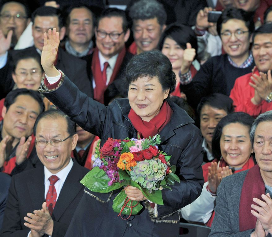 Park Geun-hye waves to supporters after arriving at the party headquarters in Seoul on Wednesday. The new South Korean president will be returning to the presidential palace where her father, Park Chung-hee, ruled for 18 years. (Associated Press)