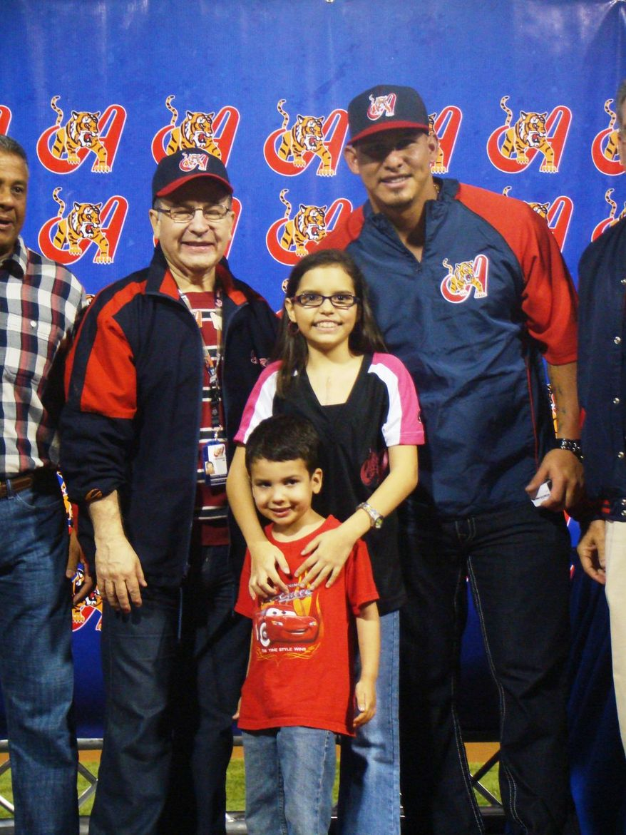 Victoria Cabrera, center, smiles with Washington Nationals catcher Wilson Ramos, right, and her younger brother, Enrique Jose, after throwing out the first pitch for the Tigres de Aragua on Monday in Venezuela. (Photo courtesy of Marfa Mata)
