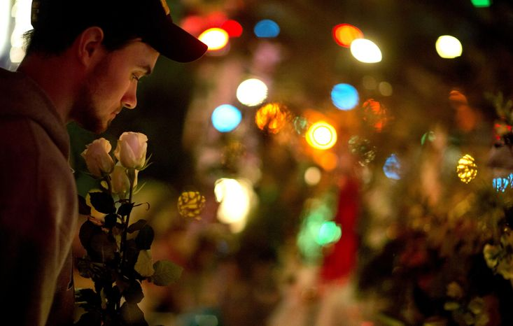A Newtown resident who identified himself only as Andrew, holds roses as he visits a memorial for the Sandy Hook Elementary School shooting victims, Tuesday, Dec. 18, 2012, in Newtown, Conn. (AP Photo/David Go