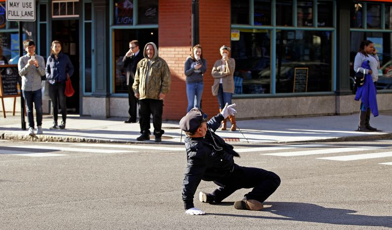 """** FILE ** Reserve Officer Tony Lepore, the """"dancing cop,"""" directs traffic on Dorrance Street in downtown Providence, R.I., on Thursday, Dec. 13, 2012. (AP Photo/Stephan Savoia)"""