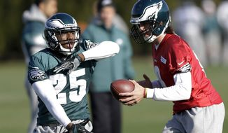 Philadelphia Eagles quarterback Nick Foles, right, fakes a handoff to running back LeSean McCoy during practice at the team's NFL football training facility, Wednesday, Dec. 19, 2012, in Philadelphia. (AP Photo/Matt Rourke)