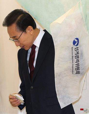 South Korean President Lee Myung-bak exits from a voting booth to cast his ballot in South Korea's presidential election at a polling station in Seoul on Wednesday, Dec. 19, 2012. South Koreans bundled in thick mufflers and parkas braved frigid weather to choose between the liberal son of North Korean refugees and the conservative daughter of a late dictator. For all their differences, the presidential candidates hold similar views on the need to engage with Pyongyang and other issues. (AP Photo/Ahn Young-joon, Pool)