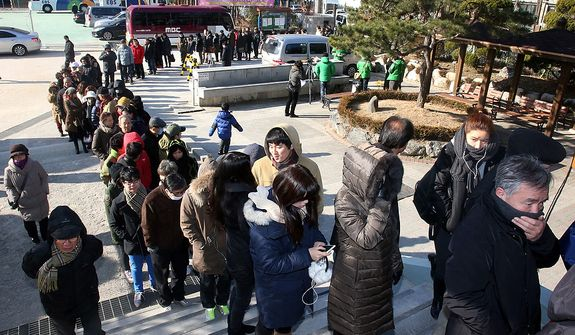 South Koreans wait in line to cast their votes in a presidential election at a polling station in Seoul on Wednesday, Dec. 19, 2012. Huge crowds turned out to vote in the tight presidential race pitting the son of North Korean refugees against the conservative daughter of a late dictator. (AP Photo/Yonhap, Kim Ju-sung)