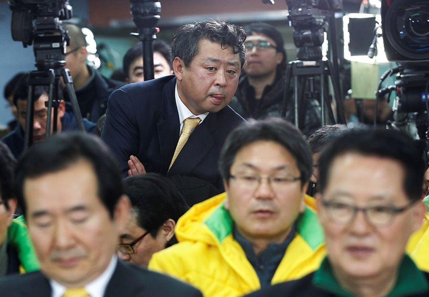 Unidentified members of the opposition Democratic United Party watch TV news reporting exit polls on their presidential candidate, Moon Jae-in, in South Korea's presidential elections at the party headquarters in Seoul on Wednesday, Dec. 19, 2012. (AP Photo/Ahn Young-joon, Pool)