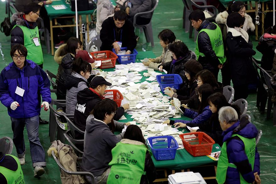 South Korean National Election Commission officials sort out ballots cast in the country's presidential election as they begin the counting process in Seoul on Wednesday, Dec. 19, 2012. South Koreans voting for president Wednesday were almost evenly divided between the conservative daughter of a late dictator and the liberal son of North Korean refugees, according to surveys released after the polls closed. (AP Photo/Lee Jin-man)