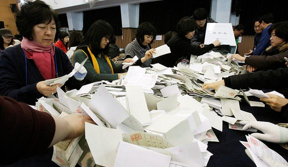 South Korean National Election Commission officials sort out ballots cast in the presidential election as they begin the counting process in Seoul on Wednesday, Dec. 19, 2012. South Koreans voting for president Wednesday were almost evenly divided between the conservative daughter of a late dictator and the liberal son of North Korean refugees, according to surveys released after the polls closed. (AP Photo/Ahn Young-joon)