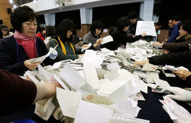 South Korean National Election Commission officials sort out ballots cast in the presidential election as they begin the counting process in Seoul on Wednesday, Dec. 19, 2012. South Koreans voting for president Wednesday were almost evenly divid