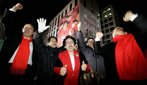 Supporters of South Korean presidential candidate Park Geun-hye of the ruling Saenuri Party cheer near the party's head office in Seoul on Wednesday, Dec. 19, 2012. South Koreans voting for president Wednesday were almost evenly divided between Miss Park, the conservative daughter of a late dictator, and Moon Jae-in, the liberal son of North Korean refugees, according to surveys released after the polls closed. (AP Photo/Lee Jin-man)